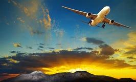 反对美丽的太阳上升的天空的平面飞行旅行的他们 免版税库存图片