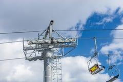 反对美丽的蓝色多云天空的空的滑雪电缆车 免版税库存图片