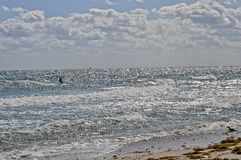 反对美丽的水和天空的风筝冲浪者 库存图片