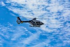 反对美好的多云天空背景的西班牙警察用直升机 免版税库存图片