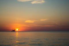 反对美好的海日落的石油平台 库存图片