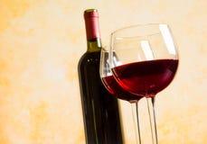 反对老墙壁背景的两块红葡萄酒玻璃 免版税库存图片