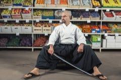 反对背景的一个人与机架用水果和蔬菜在日本举行katana的和服和hakama穿戴了 免版税库存照片