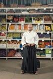 反对背景的一个人与机架用水果和蔬菜在日本举行katana的和服和hakama穿戴了 免版税图库摄影