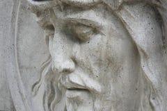 反对背景的耶稣基督雕象灰色石头(接近  免版税图库摄影
