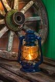 反对背景马车车轮的煤油灯 免版税库存图片