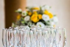 反对花花束的香宾玻璃 免版税库存照片