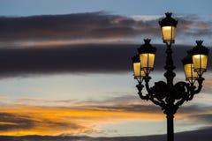 反对落日的背景的被点燃的灯笼在街道上的 免版税库存图片