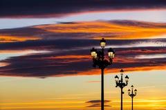 反对落日的背景的被点燃的灯笼在街道上的 免版税库存照片