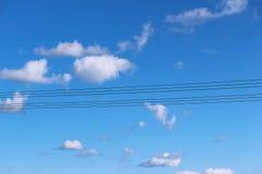 反对蓝天和云彩的六根电木杆 免版税库存图片