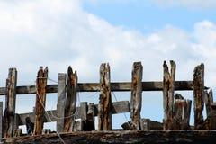 反对蓝天和白色云彩背景的老木篱芭  免版税图库摄影
