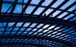 反对蓝天和阳光的玻璃屋顶 库存照片