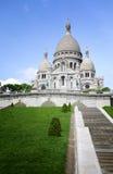 反对蓝天和绿色领域晴天, Sacre Coeur大教堂在蒙马特的在巴黎,法国 库存图片
