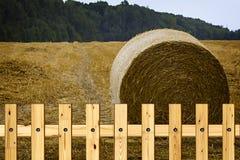 反对蓝天的一个圆的干草堆在领域 免版税库存图片