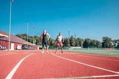 反对蓝天的两个赛跑者在体育场做准备 免版税库存照片