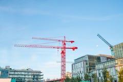反对蓝天的两台红色建筑用起重机 免版税库存照片