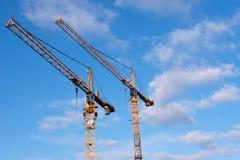 反对蓝天的两台黄色建筑用起重机与一些覆盖 图库摄影