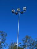 反对蓝天的体育场光 免版税库存照片