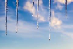 反对蓝天的冰柱与云彩 免版税库存照片
