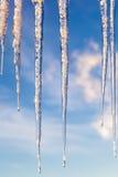 反对蓝天的冰柱与在日落的云彩 库存照片