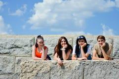 反对蓝天的四个愉快的微笑的青少年的朋友 库存照片