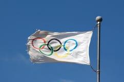 反对蓝天的奥林匹克旗子在阳光下 免版税库存照片