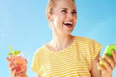 反对蓝天的妇女与刷新的鸡尾酒和智能手机 免版税库存图片