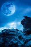 反对蓝天的巨石城与云彩和美丽的满月在 库存照片