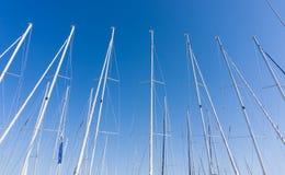 反对蓝天的帆柱,船帆柱,小游艇船坞在欧洲城市, 库存照片