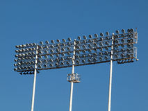 反对蓝天的强有力的体育场光 免版税库存照片