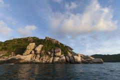 反对蓝天的扔石头的海岛海岸线与云彩 免版税库存图片