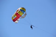 反对蓝天的明亮的降伞 免版税库存照片