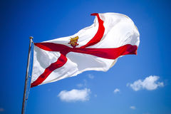 反对蓝天的海峡群岛泽西旗子 免版税库存照片