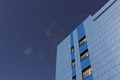 反对蓝天的现代蓝色办公楼 免版税库存照片