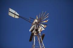 反对蓝天的生锈的老农厂风车 免版税图库摄影