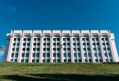 反对蓝天的白色大厦 在前景的绿草 免版税库存图片