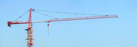 反对蓝天的红色和白色大厦塔吊 动臂起重机 免版税库存图片