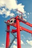 反对蓝天的红色桥式起重机细节 在圣克鲁斯de特内里费岛口岸的工业起重机 免版税图库摄影