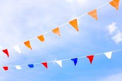 反对蓝天的红色,蓝色和白旗 免版税图库摄影