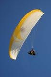 反对蓝天的纵排滑翔伞 免版税库存图片