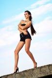 反对蓝天的美丽的年轻性感的女孩 免版税库存照片