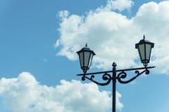 反对蓝天的老灯岗位与云彩 免版税库存照片