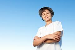 反对蓝天的英俊的十几岁的男孩常设外部 库存照片