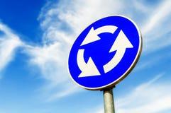 反对蓝天的蓝色环形交通枢纽交叉路公路交通标志 免版税库存照片