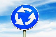 反对蓝天的蓝色环形交通枢纽交叉路公路交通标志 库存照片