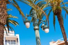 反对蓝天的街灯,在锡切斯,巴塞罗那, Catalunya,西班牙 复制文本的空间 查出在蓝色背景 免版税图库摄影