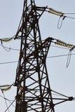 反对蓝天的高压塔 电力高装绝缘体工电压 在杆的电插孔 高压导线在天空的 库存图片