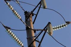 反对蓝天的高压塔 电力高装绝缘体工电压 在杆的电插孔 高压导线在天空的 免版税库存图片