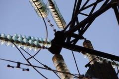 反对蓝天的高压塔 电力高装绝缘体工电压 在杆的电插孔 高压导线在天空的 免版税库存照片