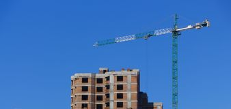 反对蓝天的黄色工业建筑用起重机 图库摄影